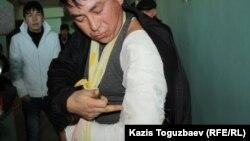 Житель Жанаозена Аманжол Ажигитов показывает забинтованную руку, раздробленную, по его словам, автоматной пулей. Актау, 18 декабря 2011 года.