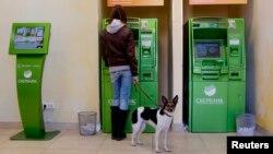 زنی در روسیه از یک خودپرداز پول دریافت میکند؛ علیرغم اقدام روز دوشنبه بانک مرکزی روسیه و تزریق شش میلیارد دلار دیگر نقدینگی، برای اولین بار ارزش واحد پول روسیه درمقابل یک دلار به ۶۴ و در یک مقابل یورو به به ۷۸ رسید.