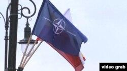 Варшава кўчаларидан бирига илинган НАТО байроғи.