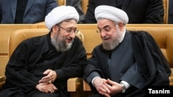 Iran's head of judiciary, Ayatollah Amoli-Larijani (L) speaking with president Hassan Rouhani. File photo