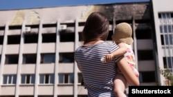 Мама з дитиною біля будівлі в Маріуполі, пошкодженої внаслідок обстрілу реактивними системами залпового вогню з боку російсько-сепаратистських сил у 2015 році