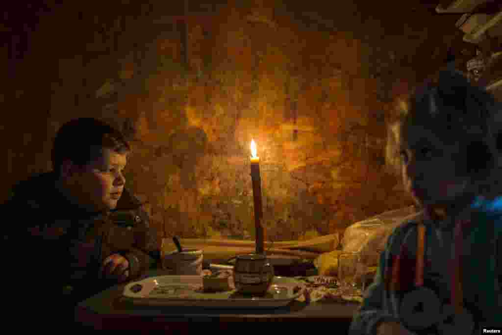 Lazar and his sister Andjelka sit by a candle in their home in the eastern Serbian town of Majdanpek. (Reuters/Marko Djurica)