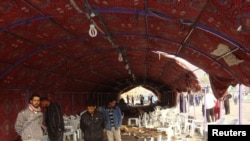 Iraqis inspect the site of a bomb attack inside a funeral tent in Baghdad's Shula district on January 27.