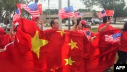 U.S. -- A group of China supporters wave Chinese and US flags as they wait for the arrival of Chinese President Xi Jinping at Palm Beach international airport, April 06 2017
