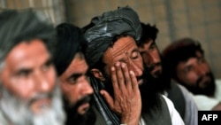 Afghans discuss security at a local council meeting in Helmand Province in June 2010.