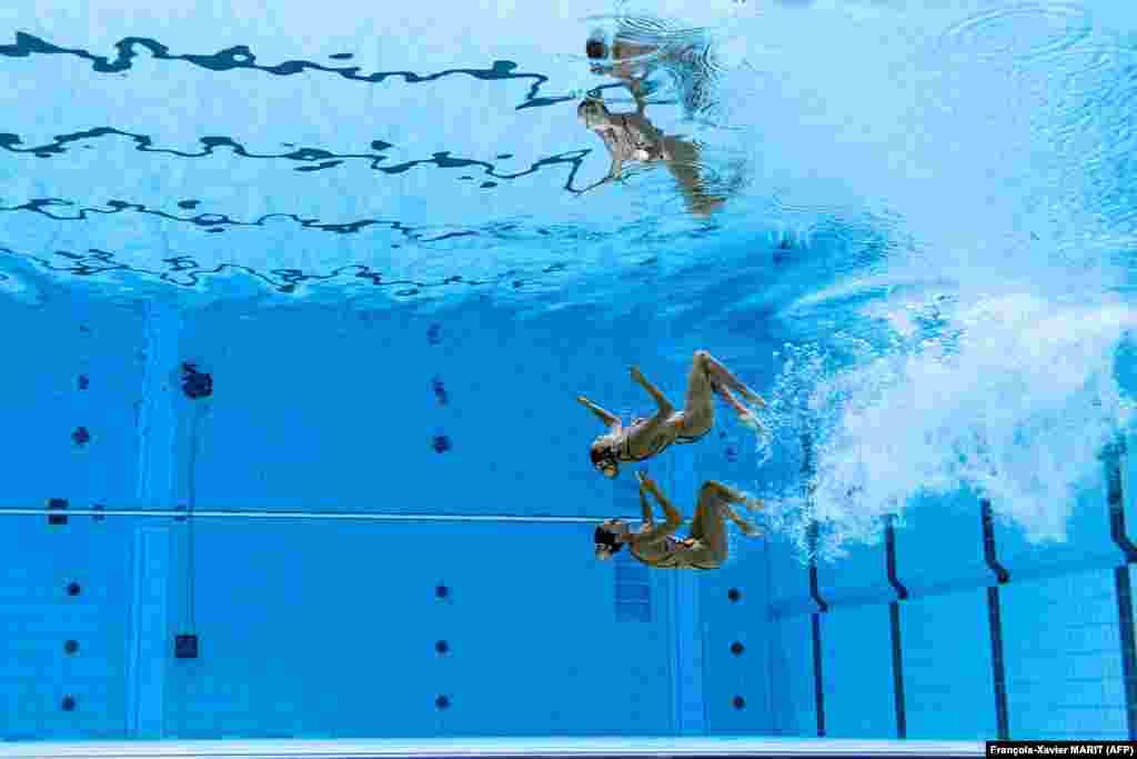 Сууда көркөм сүзүү боюнча мелдештер бассейнде өтөт. Мында спортчулар музыканын коштоосунда синхрондуу түрдө ар түрдүү кыймыл аракеттерди жасашат.