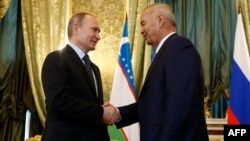 Russian President Vladimir Putin (left) meets with Uzbek President Islam Karimov at the Kremlin in Moscow on April 26.
