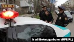 Корреспондент Азаттыка Кенжебек Тыныбаев под наблюдением полицейских пишет объяснительную о произошедшем. Алматы, 29 марта 2015 года.