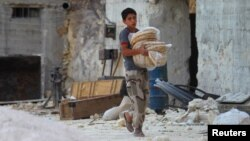 A boy carries bread as he walks in Latamneh city, which was hit by Russian air strikes, in the northern countryside of Hama.