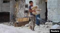 A boy carries bread in the Syrian city of Latamneh, which was reportedly hit two days ago by Russian air strikes.