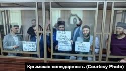 Фигуранты второго Бахчисарайского «дела Хизб ут-Тахрир» подняли в зале Южного окружного военного суда плакаты, приуроченные к годовщине депортации крымских татар 18 мая 1944 года. Ростов-на-Дону, 18 мая 2020 года