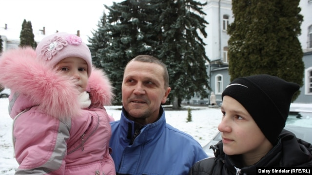 Ihor, 51, reporting for army training in Lviv with his 2-year-old daughter, Bozhenka, and his 14-year-old son, Nazar.