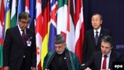 Anders Fogh Rasmussen și Hamid Karzai semnînd parteneriatul NATO-Afganistan