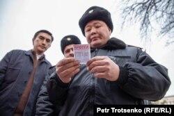 Сотрудник полиции проверяет документы у журналистов. Алматы, 22 февраля 2020 года.