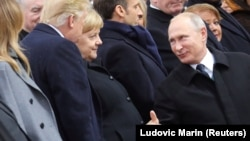 Russian President Vladimir Putin (right) greets German Chancellor Angela Merkel and U.S. President Donald Trump as they attend a commemoration ceremony for Armistice Day in Paris on November 11.