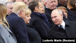 Russian President Vladimir Putin talks with German Chancellor Angela Merkel and U.S. President Donald Trump as they attend a commemoration ceremony for Armistice Day, 100 years after the end of the First World War at the Arc de Triomphe, in Pari