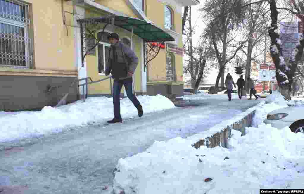 Жаяу жүргінші көктайғақ мұзға айналған тротуардың үстімен кетіп барады