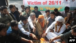 Students in Delhi on November 26 pray for victims of the Mumbai terror attacks one year earlier.