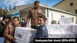 Afghan health workers unload coronavirus vaccines at Kabul airport.