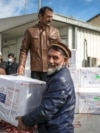 Afghan healthcare workers unload the first shipment of COVID-19 vaccines donated by the Indian government at the Kabul airport on February 7.