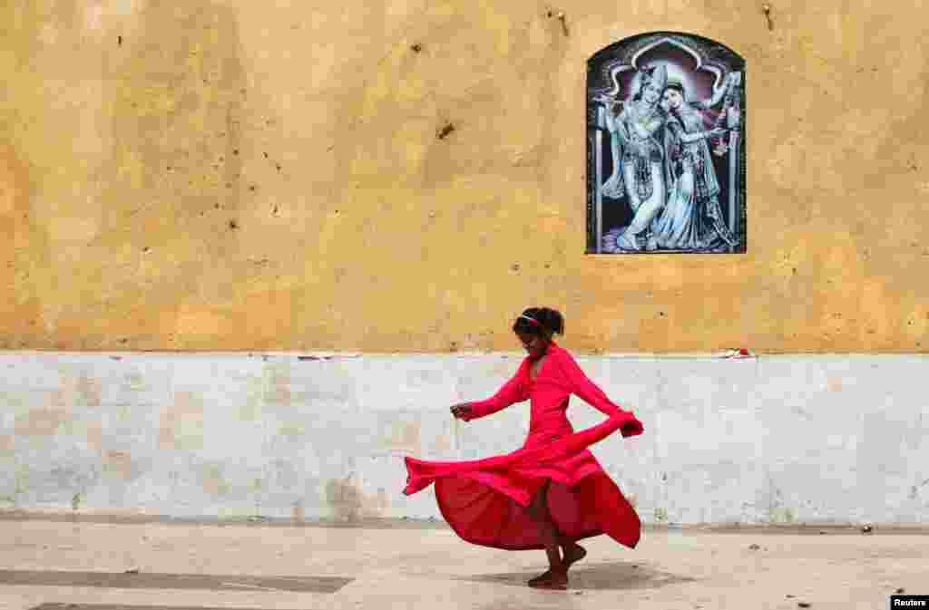 A Pakistani Hindu girl plays near a wall adorned with a religious image outside the Shri Swaminarayan Temple in Karachi. (Reuters/Akhtar Soomro)