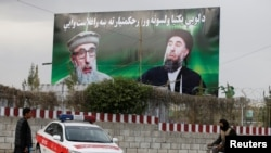 FILE: An Afghan man rides on his bicycle past a banner with pictures of Gulbuddin Hekmatyar in Kabul.