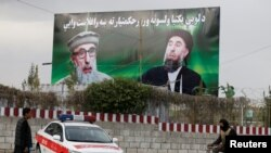 An Afghan man rides on his bicycle past a banner with pictures of Gulbuddin Hekmatyar in Kabul on May 2.