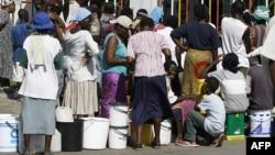 Женщины и дети стоят в очереди за водой в столице Зимбабве. Хараре, 1 декабря 2008 года.