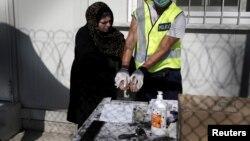 Ілюстраційне фото, біженка з Афганістану у Греції здає відбитки пальців