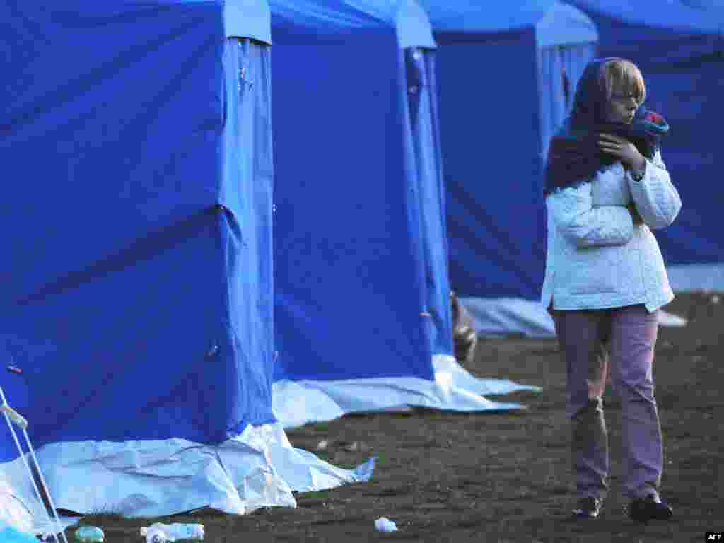 Italy -- A woman wakes up after spending the night at a stadium in the Abruzzo capital of L'Aquila, 07Apr2009 - ITALY, L'Aquila : People wake up on April 7, 2009 after spending the night in a stadium in the Abruzzo capital of L'Aquila, the epicenter of an earthquake that struck on April 6. The death toll from the powerful quake that rocked central Italy has risen to 179, with 34 people reported missing, rescue workers in the town of L'Aquila said on April 7.