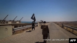 A video grab allegedly shows Islamic State (IS) militants waving the trademark Jihadist flag near Mosul, Iraq