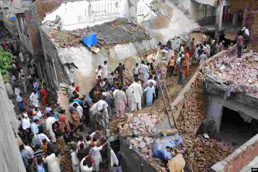 Rescue workers and residents search for worshippers in the rubble of a collapsed mosque in Lahore. Twenty-four worshippers were killed when the roof collapsed after heavy rain.