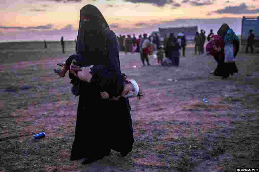 A woman carries her injured child as she walks to members of the Kurdish-led Syrian Democratic Forces (SDF) just after leaving the Islamic State group's last holdout of Baghouz in the eastern Syrian Deir Ezzor Province. (AFP/Bulent Kilic)