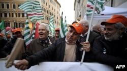 Демонстранты перед зданием итальянского парламента с флагами профсоюзов бастуют против правительственных мер жесткой экономии. Рим, 12 декабря 2011 года.