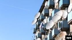 Спутниковые антенны на фасаде многоэтажного дома в городе Байконуре. 3 ноября 2013 года.