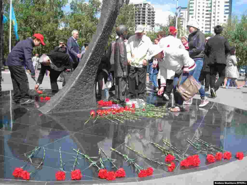 «1932-1933 жылдардағы ашаршылық құрбандарына тағзым» монументіне гүл қойып жатқан тұрғындар. Астана, 31 мамыр 2014 жыл.