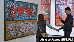 Посетители выставки рассматривают полотно Оразбека Есенбаева «Круговорот еды в природе». Алматы, 10 апреля 2019 года.