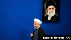 Iranian President Hassan Rouhani walks past a picture of the Supreme Leader Ayatollah Ali Khamenei as he arrives to a press conference at the presidency compound in Tehran, Iran, Monday, April, 10, 2017.