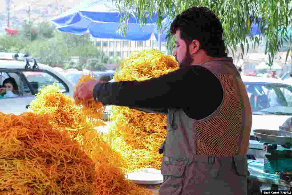 An Afghan prepares special Eid treats for customers in Kabul's Pule Baghe Omomi open-air market.