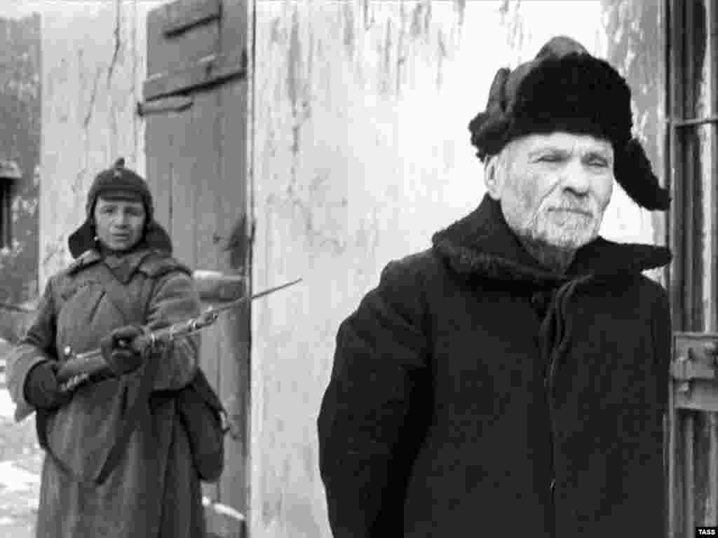 "By the 1930s the hat was being phased out and replaced by the warmer ushanka fur caps, as worn by this ""traitor"" being arrested by a budyonovka-wearing communist in a 1938 propaganda photo."