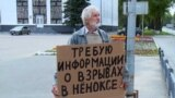 RUSSIA -- In this screenshot taken from the August 13 nightly news program broadcast by the Severodvinsk TV, in the Arkhangelsk region city of Severodvinsk, an unidentified man stands outside the city administration building, holding a cardboard sign read