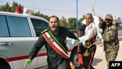 Иранские военные несут раненого в результате стрельбы на параде в городе Ахваз. 22 сентября 2018 года.