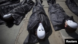 Campaigners from the Control Arms NGO lie in fake body bags to demonstrate in front of the UN building in New York earlier this month.