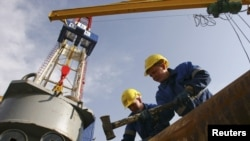 Workers prepare equipment on the drilling tower of the Shakhrinav-1P exploratory well at the Sarikamysh gas field in Tajikistan.