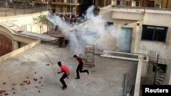 شابان من المصريين الأقباط يركضان على سطح الكنيسة الرئيسة في القاهرة بعد أن أطلقت قوات الأمن قنابل الغاز أثناء إشتباكات مع مسلمين خارج الكنيسة.