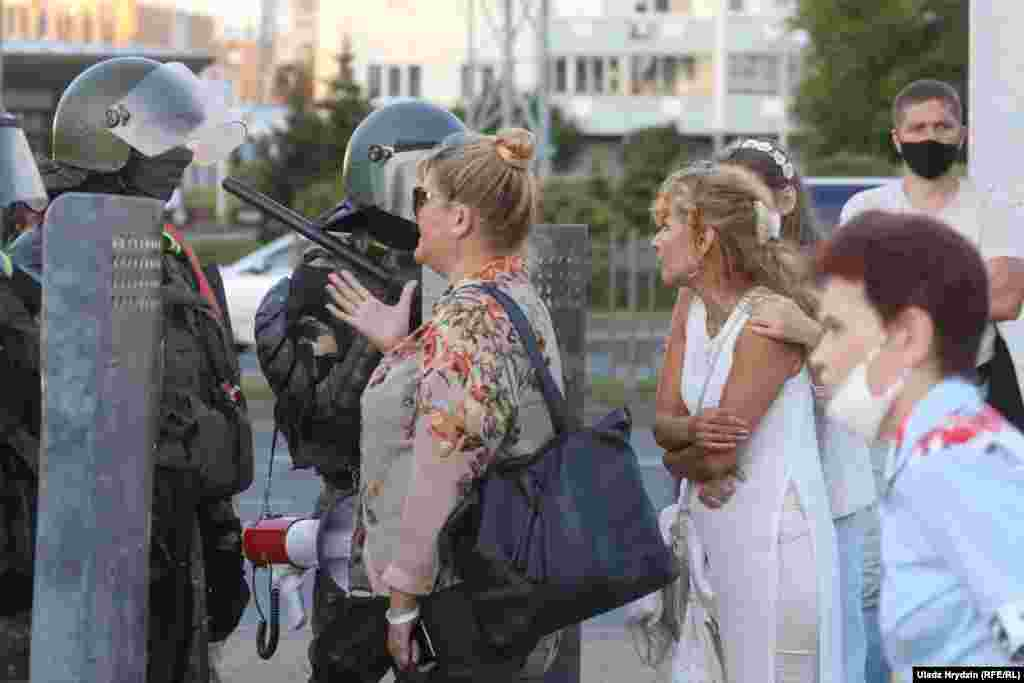 People talk to Belarusian law enforcement officers in Minsk on August 11.