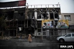 People walk past buildings which burned during protests that followed the authorities' decision to raise gasoline prices, in the city of Karaj, November 18, 2019
