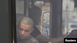 Мигрант, задержанный в ходе рейда в Красноярске, смотрит из окна полицейского автобуса. 7 августа 2013 года.