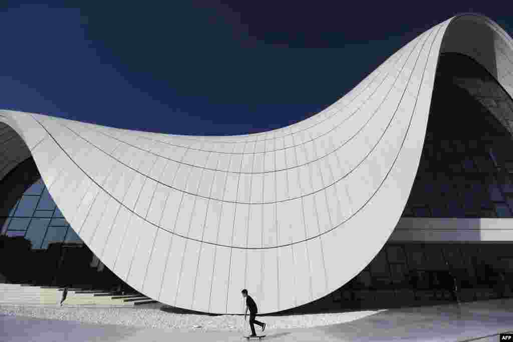 A child skateboards in front of the Heydar Aliyev Center in Baku. (AFP/Benjamin Cremel)
