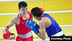 Казахстанский боксер Абылайхан Жусупов (в красной форме) на отборочном олимпийском турнире в Китае. 26 марта 2016 года.